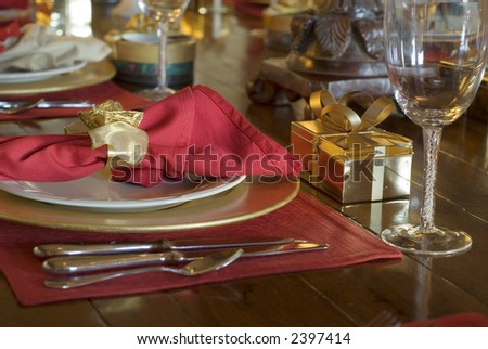 gift box at table setting with silverware and dinner plates and wine glasses