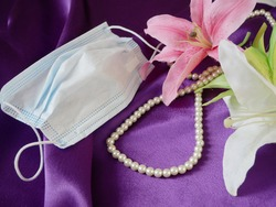gift box, blue medical mask, golden wedding rings, pearls necklace and pink flowers bunch, Wedding and coronavirus concept