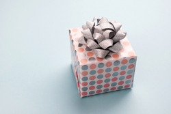 Gift box in colored peach-gray peas with a silver bow on light blue background
