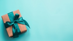 Gift box in craft wrapping paper and green satin ribbon on turquoise blue background, copy space right. Beautiful Christmas, New Year or Birthday present, flat lay or top view. Banner