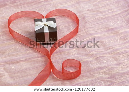 Gift box in red heart shaped ribbon. Horizontal composition.