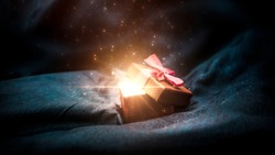Gift box on a dark magic background with light bokeh. Festive background, magic box with a gift. Dark abstract background with gold bokeh.