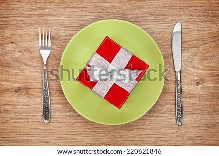 Gift box on plate and silverware over wooden table background