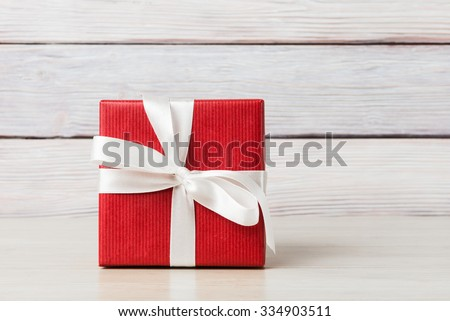 Gift box over light wooden background #334903511