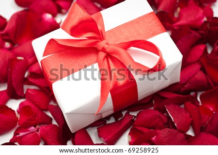 Gift box over red colorful rose petals