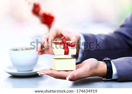 Gift box / present or valentine gift hand close up. Decorative gift box tied with a turquoise ribbon and bow carefully cupped in female hand as she gives a surprise present to a loved one