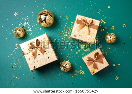 Gift box, shiny gold disco balls, sparkling gold glitter on green background. New year baubles, star sparkles. New year, Christmas, Valentine's day concept of greetings. Copy text. Top view, flat lay.