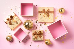 Gift box, shiny gold disco balls, sparkling gold glitter on pink background. New year baubles, star sparkles. New year, Christmas, Valentine's day concept of greetings. Copy text. Top view, flat lay.