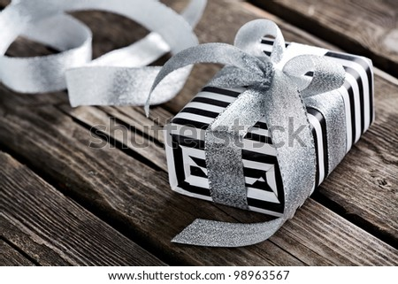 Gift box tied big silver bow with curved silver ribbon on old wooden background.