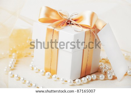 Gift box tied with gold ribbon with gift card and pearl necklace.