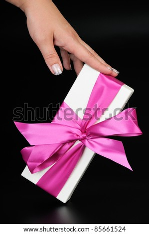 Gift box with a big pink bow and woman's hand. On a dark background.