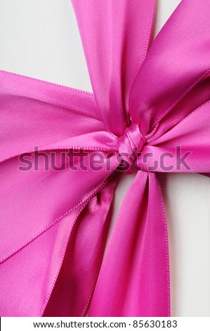 Gift box with a big pink bow close up. On a dark background.