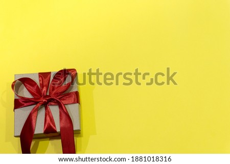 Gift box with a red ribbon on a yellow background. Illuminating. Color of the year 2021. milimalism. Concept of sales, shopping, valentines day, christmas holidays and birthday