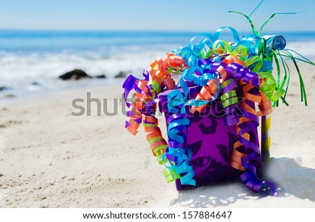 Gift box with Birthday decorations on the sandy beach by the ocean