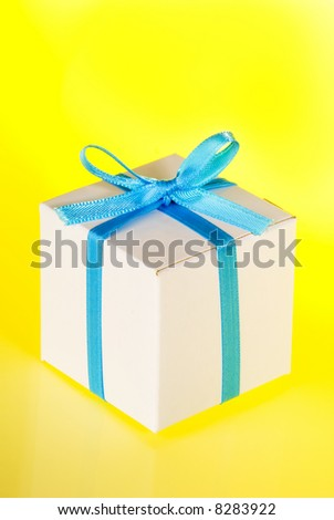 Gift Box with Blue Ribbon against Yellow