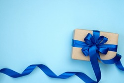 Gift box with blue ribbon bow isolated on blue background. Present for Father's Day, Birthday or international Men's day Day. Festive decor background. Top view flat lay with free space.