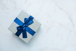 Gift box with blue ribbon on white marble background. Gifts, celebration, valentines theme