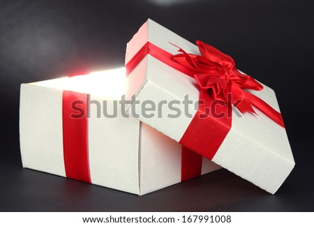 Gift box with bright light on it on dark grey background