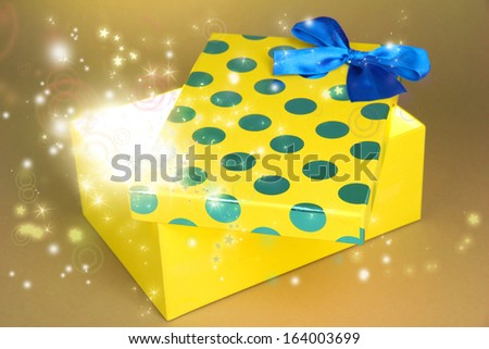 Gift box with bright light on it on yellow background