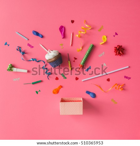 Gift box with colorful party items on pink background. Flat lay.