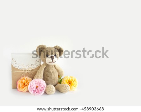 Gift box with crochet teddy bear doll and rose flower on white background #458903668