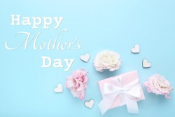 Gift box with eustoma flowers and text Happy Mothers Day on blue background