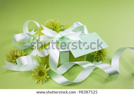 Gift box with flowers on green background