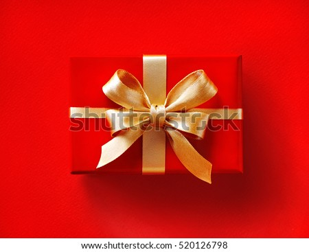 Gift box with golden ribbon on red background. Close up. Top view. High resolution product