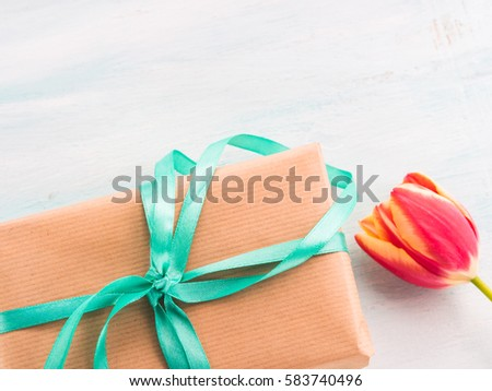 Gift box with green ribbon on pastel spring background. Copy space top view father's mother woman day Easter special occasion present #583740496