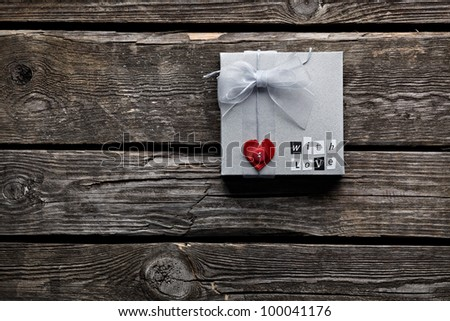 Gift box with heart shape and tied with organza ribbon on old vintage wooden background.