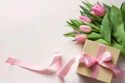 Gift box with long pink ribbon and tulips on light background