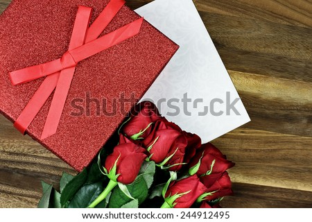 Gift box with long stem red roses and card over an old wooden background with room for copyspace.