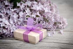 Gift box with purple bow and lilac on wood
