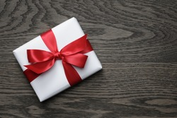 gift box with red bow on wood table, top view
