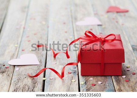 Gift box with red bow ribbon and paper heart on wooden table for Valentines day