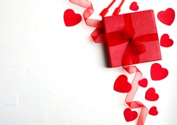 Gift box with red ribbon, many decorative red hearts and candle on textured white background. Festive background. Flat lay with copy space.