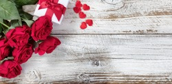 Gift box with red roses and hearts on rustic wood in flat lay view