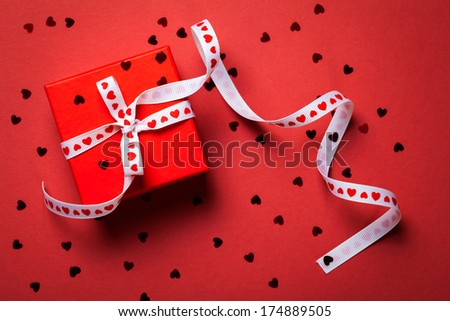 Gift box with ribbon on red paper background. Valentines Day . Top view