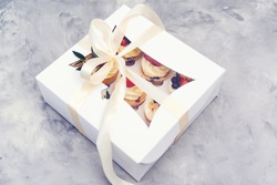 Gift box with tasty cupcakes. Present box full of fruit cupcakes. Birthday party. Easter or christmas holidays celebrate. Holidays cupcakes with strawberry and blueberry. Cupcake packaging. Delivery.