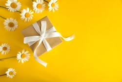 Gift box with white ribbon  and chamomile on the yellow background.Top view.