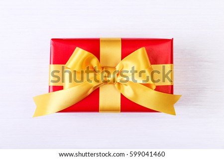 Gift box with yellow bow. Present wrapped with ribbon. Christmas or birthday red package. On white wooden table. #599041460
