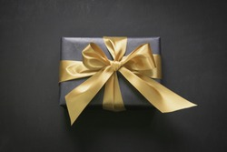 Gift box wrapped in black paper with gold ribbon on black surface. Top view.