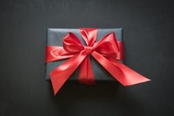Gift box wrapped in black paper with red ribbon on black surface. Top view.