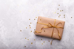 Gift box wrapped in craft paper with gold ribbon and stars on grey stone