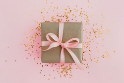 Gift box wrapped in craft paper with pink ribbon on pale pink background with glitters. Festive concept, top view.