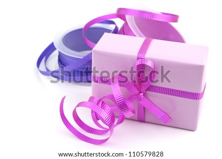 Gift box wrapped in pink wrapping paper and purple curly ribbon isolated on white background.