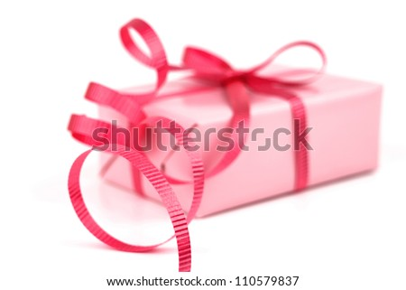 Gift box wrapped in pink wrapping paper and red curly ribbon isolated on white background.