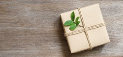 gift box wrapped in recycled paper with rope and leaf on wood background with copy space for text or image , green concept