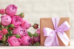 Gift box wrapped with craft paper and pink bow on pink roses background. Happy Birthday, Women day, Mother day, Holiday concept.
