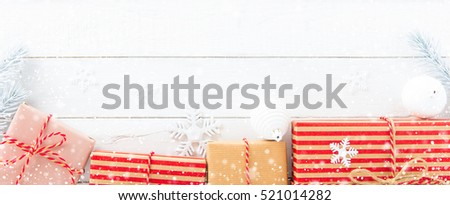 Gift boxes and Christmas ornaments on white wood background, border design panoramic banner